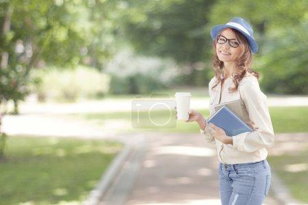 Photo pour Joyeux jeune étudiant avec un café à emporter, marchant dans un parc d'été et tenant des livres pour lire et étudier . - image libre de droit
