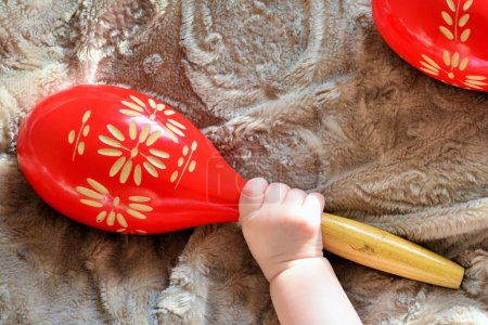 Baby hand with red wooden maracas