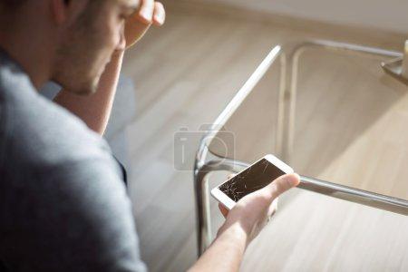 Woeful man holding damaged smart phone