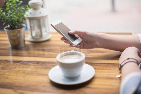 Photo pour Envoyer des SMS sur un téléphone intelligent tout en buvant café - image libre de droit