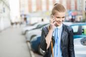 Usmívající se žena na telefonu v centru města