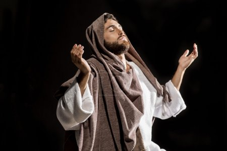 Photo for Jesus Christ praying to God with open arms in the dark black night - Royalty Free Image