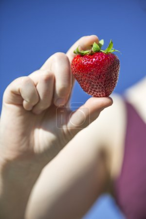Big strawberry holding by woman in front of blue sky