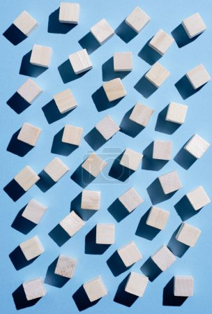 Wooden cubes spread over blue