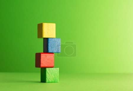 Photo for Colorful wooden cubes stacked over green, background - Royalty Free Image