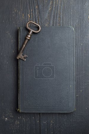 Photo for Vintage Key on black leather book cover and wooden table, top view - Royalty Free Image