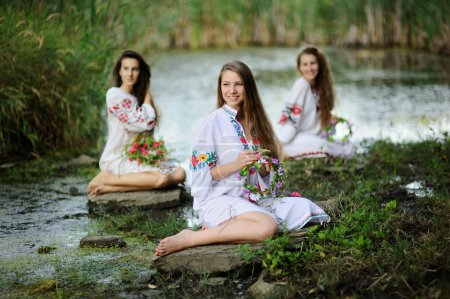 three girls in the Ukrainian national clothes with wreaths of fl