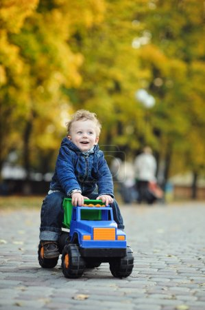 Photo for Little boy with curly hair riding a toy car on a background of autumn trees. The boy laughs - Royalty Free Image