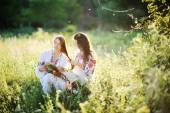 Two girls in Ukrainian national dress sitting on the grass. Girl