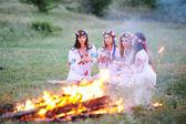 Ukrainische Mädchen im Hemd sitzen um das Lagerfeuer
