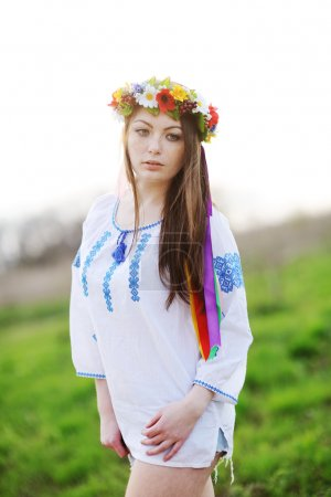 Photo for Ukrainian girl in a shirt and a wreath of flowers and ribbons on his head on a background of green grass - Royalty Free Image