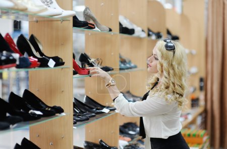 Beautiful girl chooses shoes in a shoe store