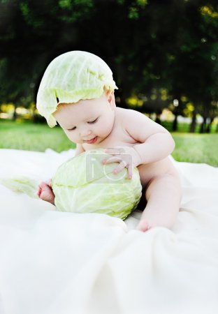baby girl with cabbage. Cabbage leaves on the head of a child. Child relaxing in a park on the grass.