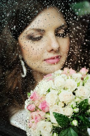 Portrait of a girl behind wet glass. The bride in a wedding car