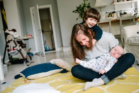 Young and happy mother playing with her small children on the floor of the house. Children laugh. Concept of family