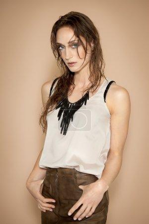 Photo pour Modèle de mode avec cheveux mouillés portant un top en soie crème et une jupe en cuir marron au mur beige . - image libre de droit