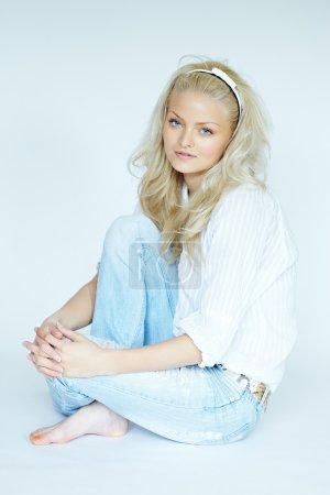 Photo pour Jeune femme blonde portant un jean et une blouse blanche. Certaines images de la série sont prises avec un objectif inclinable et décalé . - image libre de droit