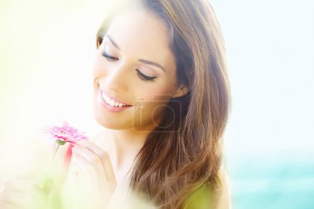 Photo for Smiling girl with pink daisy outdoors. Bokeh and light leak created in-camera. - Royalty Free Image