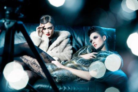 Photo pour Deux modèles tristes fatigués assis sous les projecteurs . - image libre de droit