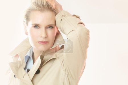 Photo pour Belle femme élégante moderne à l'intérieur utilisant le trench-coat dans le studio. - image libre de droit