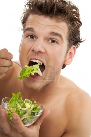 Photo for Young fit man eating raw green healthy vegetarian salad in glass bowl. - Royalty Free Image