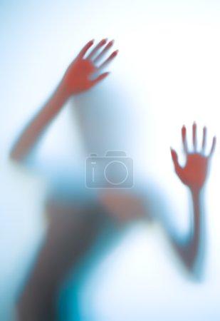 Photo pour Silhouette féminine dans des tons cyan derrière un verre brumeux . - image libre de droit