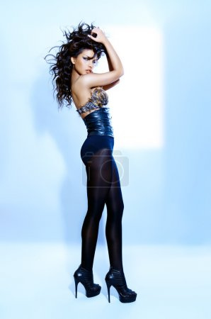 Photo pour Young woman wearing a black outfit with leather and feathers. - image libre de droit