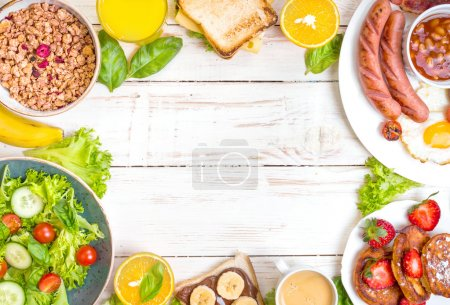 Photo for Assortment of breakfast choices. English breakfast, sausages, fried eggs, bacon, salad, granola, cheese sandwich, pancakes, chocolate cream and banana toast, coffee, fresh orange juice. Space for text - Royalty Free Image