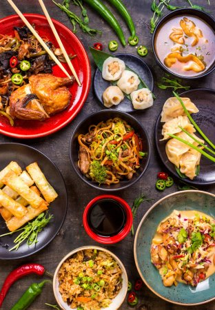 Photo for Assorted Chinese food set. Chinese noodles, fried rice, dumplings, peking duck, dim sum, spring rolls. Famous Chinese cuisine dishes on table. Top view. Chinese restaurant concept. Asian style banquet - Royalty Free Image