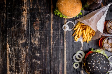 Photo for Set of black burgers with meat patty, cheese, tomatoes, mayonnaise, french fries and glass of cold cola soda with ice from above. Dark wooden rustic background. Space for text. Top view - Royalty Free Image