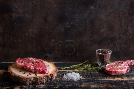 Raw meat steak on dark wooden background ready to ...