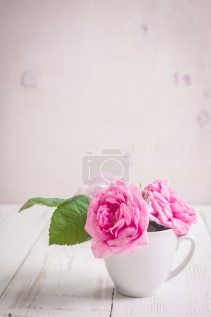 Photo for Beautiful pink tea roses on a white wooden background. Romantic background. Rustic shabby frame - Royalty Free Image