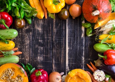 Photo for Fresh vegetables on a old rustic dark textured table. Autumn background. Healthy eating frame. Sliced pumpkin, zucchini, squash, bell peppers, carrots, onions, cut garlic, tomatoes, eggplant, corn cob, rucola and basil. Top view. Space for text - Royalty Free Image