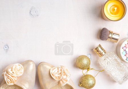 Photo for Holiday feminine cosmetic background in golden colour. Cosmetic objects frame with gold heels, gold glitter christmas balls, perfume bottle, burning candle, meteorites powder and brush. Getting ready for a party - Royalty Free Image