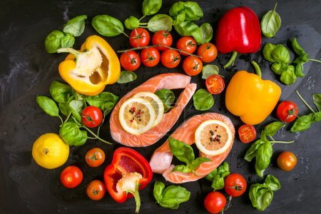 Photo for Raw salmon steaks with lemon slices and fresh cherry tomatoes, bell pepper, basil leaves and dry pepper. Ingredients for cooking on a dark background. Healthy and diet food concept. Top view - Royalty Free Image