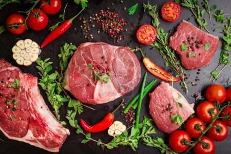 Photo for Different types of steaks set. Assorted raw meat on a black chalk board background. Rib eye steak on the bone, veal shank (ossobuco), fillet with cherry tomatoes, hot pepper and herbs. - Royalty Free Image