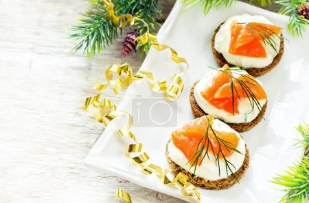 Photo for Canape with salmon and cream cheese with dill for Christmas on a light woody background. tinting. selective focus on the front canapes - Royalty Free Image