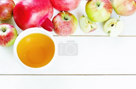 Photo for Apples, honey and pomegranates on a light wood background, traditional food for the Jewish new year. Rosh Hashana. selective focus on the middle of the honey - Royalty Free Image