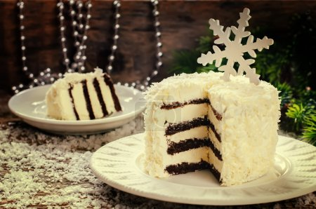 Photo for Coconut chocolate cake with butter cream on a dark wood background. tinting. selective focus on a snowflake - Royalty Free Image