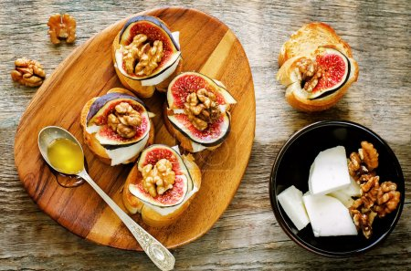 Photo for Bruschetta with figs, honey, goat cheese and walnuts on a dark wood background. tinting. selective focus on walnut on the right bruschetta - Royalty Free Image