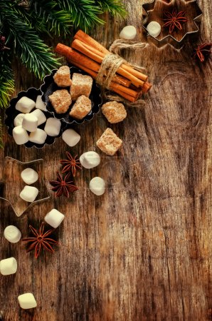 Photo for Christmas baking ingredients on a dark wood background. tinting. selective focus on the middle of the cinnamon - Royalty Free Image