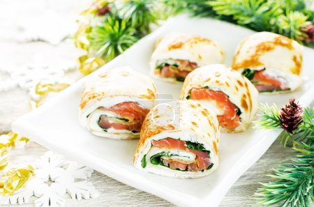 Photo for Rolls with salmon, spinach and cream cheese on a light woody background. tinting. selective focus on the front roll - Royalty Free Image