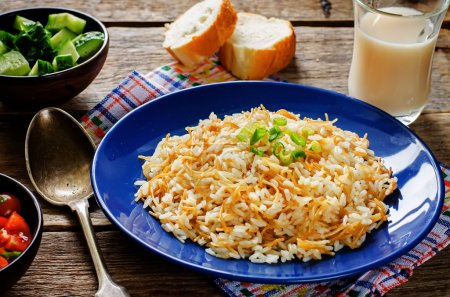 Photo pour Rice with vermicelli on a dark wood background. Traditional Arabic dish. tinting. selective focus on green onions - image libre de droit