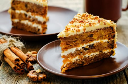 Photo for Carrot cake with walnuts, prunes and dried apricots on a dark wood background. tinting. selective focus - Royalty Free Image