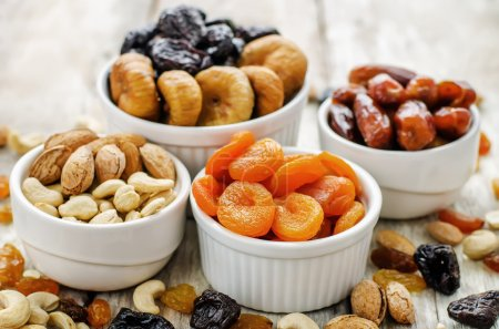 Photo for Mix of dried fruits and nuts on a white wood background. tinting. selective focus - Royalty Free Image
