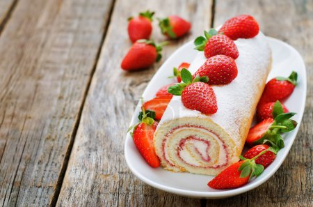 Photo for Cake roll with strawberries and cream cheese on a dark wood background. tinting. selective focus - Royalty Free Image