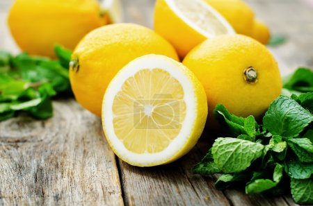 Photo for Lemons and mint on a dark wood background. tinting. selective focus - Royalty Free Image
