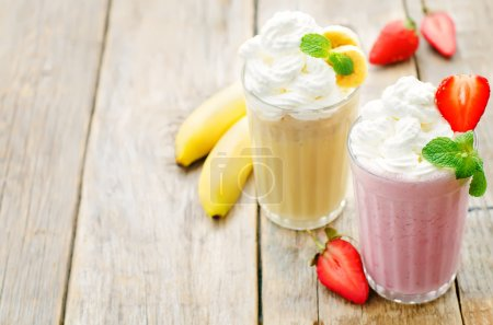 Photo for Strawberry and banana milkshake with whipped cream on a dark wood background. tinting. selective focus - Royalty Free Image