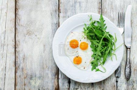 Photo pour Petit déjeuner frais avec les oeufs brouillés et à la roquette sur un fond de bois blanc. teinter. mise au point sélective - image libre de droit