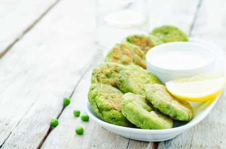 Photo for Fritters green peas with yogurt sauce and lemon on a white wood background. tinting. selective focus - Royalty Free Image